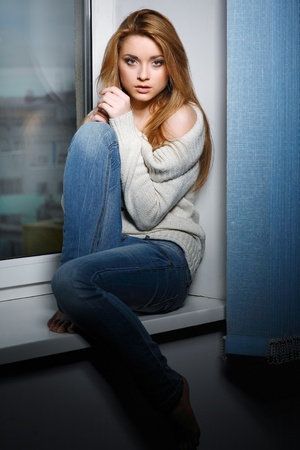 women jeans: Beautiful long-haired girl, sitting on a window-sill Stock Photo