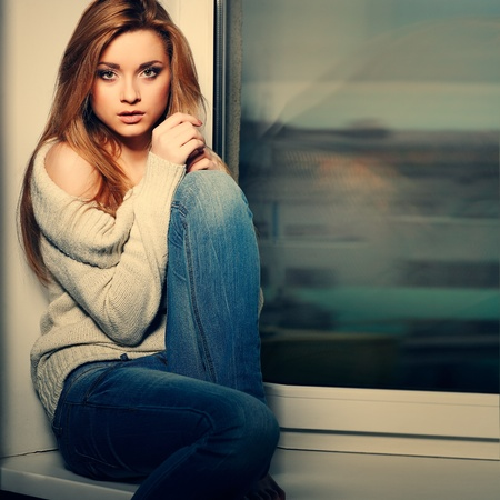 Beautiful long-haired girl, sitting on a window-sill photo