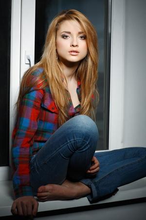 m�lancolie: Belle aux cheveux longs jeune fille, assise sur un rebord de la fen�tre