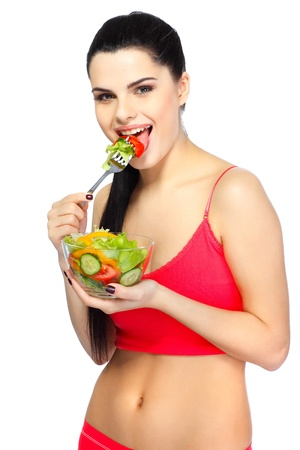Portrait of a pretty young woman eating vegetable salad isolated on  a white background photo