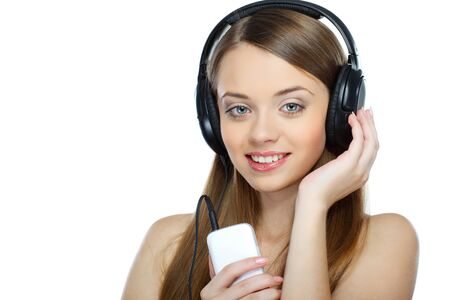 Beautiful girl with headphones listening music isolated on a white background photo