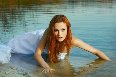 Beautiful redheaded woman in a wedding-dress in water photo