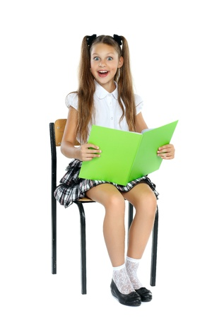 sits on a chair: a little girl is in a school form which sits on a chair and reads an interesting book. Isolated on a white background Stock Photo