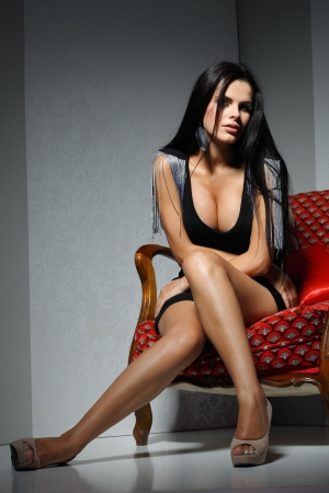 Sexual  girl with dark hairs, sitting on a red arm-chair