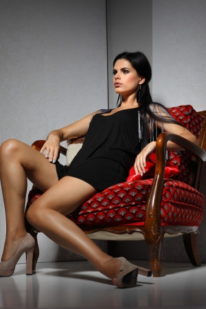 Sexual  girl with dark hairs, sitting on a red arm-chair photo