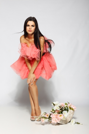 Beautiful sexual brunette in pink clothes with the basket of flowers photo