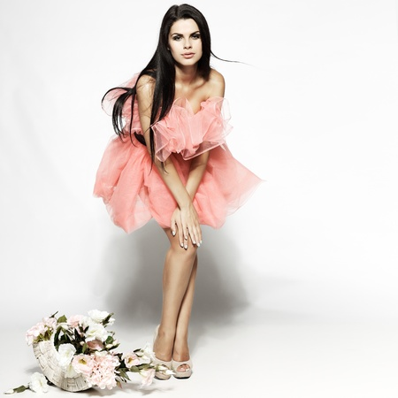 high fashion: Beautiful sexual brunette in pink clothes with the basket of flowers