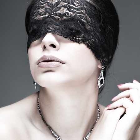 portrait elegant sexual  brunette woman is in a black lace mask photo