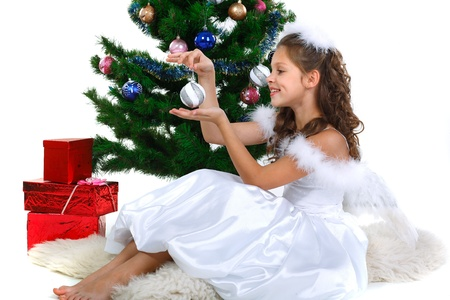 miracle tree: Little beautiful girl near a christmas tree isolated on a white background Stock Photo