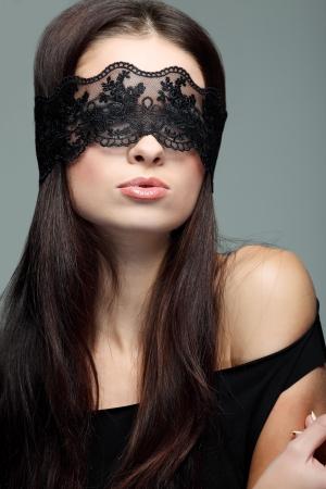 portrait elegant sexual  brunette woman is in a black lace mask photo
