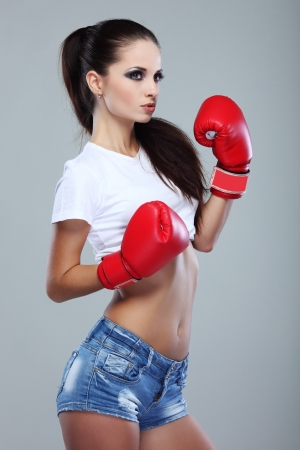 short gloves: Beautiful sexual boxing girl, fitness, on a grey background