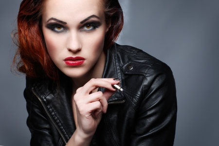 a portrait of beautiful sexual redheaded girl is in a black leather jacket, smoking a cigarette photo