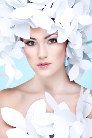 Wonderful girl in a hat from paper white butterflies  On a blue background  Beauty Face photo