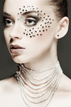 Portrait of sexual beautiful girl with strasses on face, on a dark-grey background photo