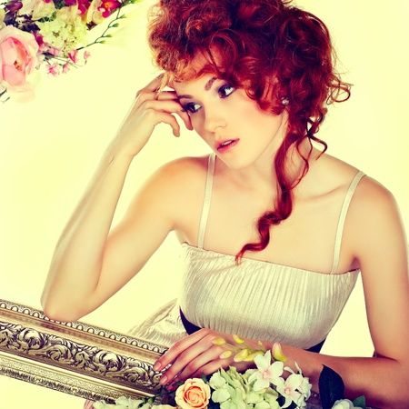 Beautiful redheaded girl with the bouquet of tulips, which stands in a gold frame, flowered, isolated on a white background photo