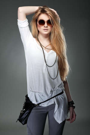 A photo of beautiful girl is in fashion style on  grey  background, glamour photo