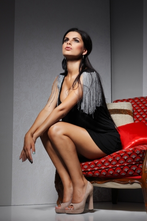 arm chair: Sexual  girl with dark hairs, sitting on a red arm-chair