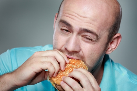 Funny man eating hamburger on grey background Stock Photo - 21531359