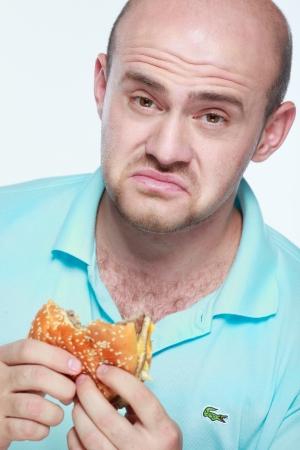 avid: Funny man eating hamburger on grey background Stock Photo