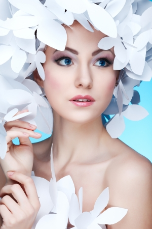 Wonderful girl in a hat from paper white butterflies. On a blue background. Beauty Face photo