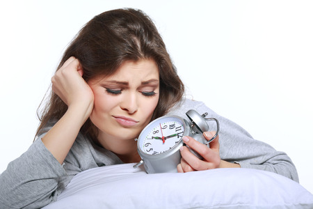likable: happy positive young  woman waking up and switching off the alarm clock Stock Photo
