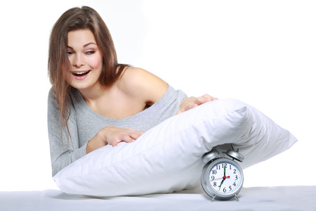 belongings: happy positive young  woman waking up and switching off the alarm clock Stock Photo