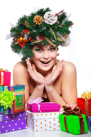 Christmas Woman. Beautiful New Year and Christmas Tree Holiday Hairstyle and Make up. photo