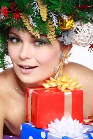 exemplary: Christmas Woman. Beautiful New Year and Christmas Tree Holiday Hairstyle and Make up.