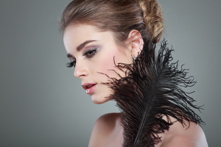 Closeup portrait of sexy whiteheaded young woman with black feather  on grey  background photo