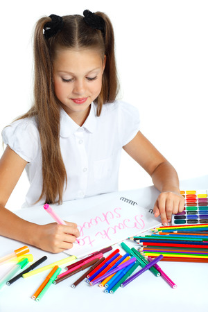 A beautiful girl in a school form drawing a marker, isolated on a white background photo