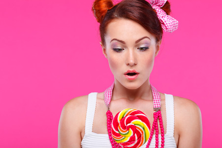 varicoloured: Portrait of beautiful  merry redheaded girl with a large candy on a pink background