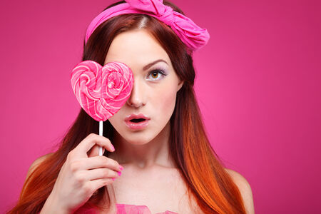 pink lips: Portrait of beautiful  merry redheaded girl with a large candy on a pink background
