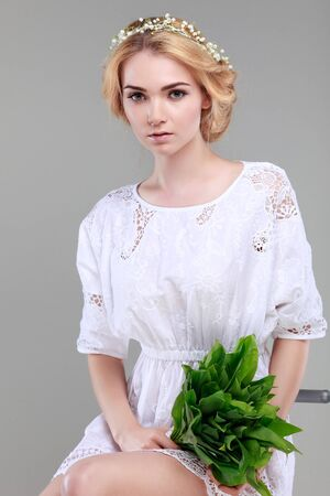 naivety: Beautiful sexual blonde  in white  clothes with the basket of flowers  on a grey background Stock Photo