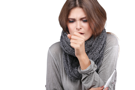 coldly: woman taking her temperature wile feeling sick and with fever, isolated on a white background Stock Photo
