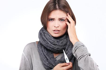fiebre: mujer que toma su sentimiento wile temperatura enfermo y con fiebre, aislado en un fondo blanco
