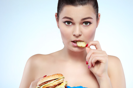 Funny girl eating hamburger on grey background Stock Photo