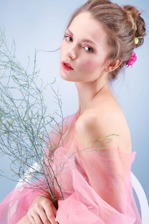 Beautiful girl, isolated on a blue background with varicoloured flowers, emotions, cosmetics