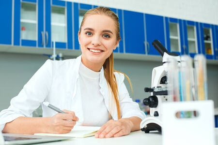 Young chemistry teacher in school laboratory workplace writing project