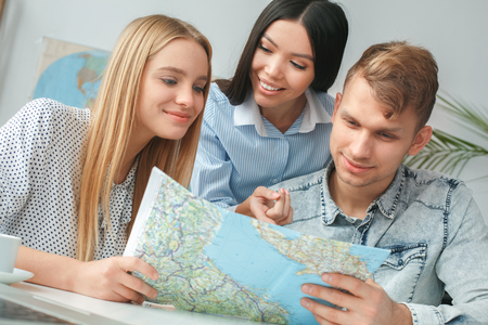 Young couple in a tour agency communication with a travel agent travelling concept choosing destination on a map