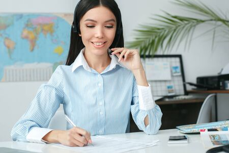 Young female travel agent consultant in tour agency writing and communicate using headset Stock Photo