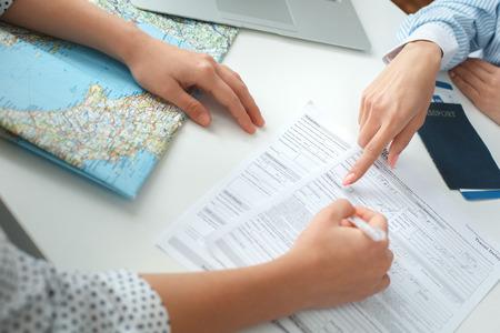 Jonge vrouwelijke reisbureauadviseur in reisbureau met een klant die documenten ondertekent Stockfoto