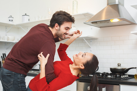 Young couple having romantic evening at home in the kitchen dancing Stock Photo