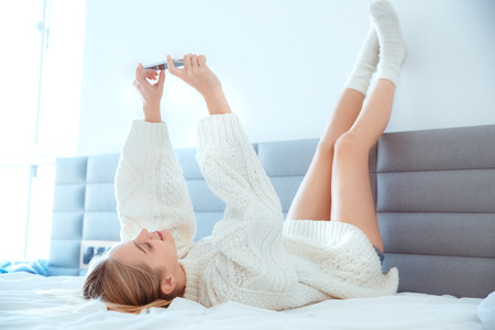 Young woman at home laying legs up on wall in bed wearing sweater selfie pictures Imagens
