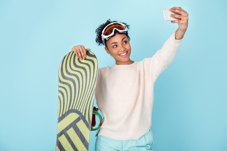 Young african woman isolated on blue wall studio winter sport snowboarding concept selfie photos Stock Photo