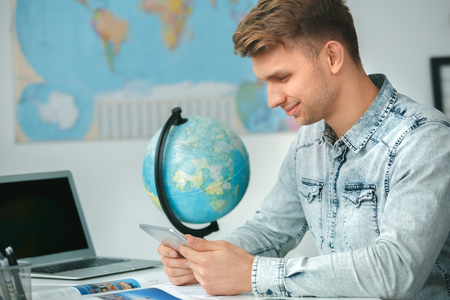 Young male travel agent consultant in tour agency playing digital tablet Stock Photo