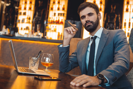 Businessman sitting in a business center bar smoking cigar