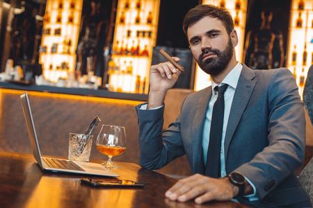 Businessman sitting in a business center bar smoking cigar