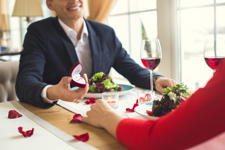 Young couple having romantic dinner in the restaurant proposal ring close-up