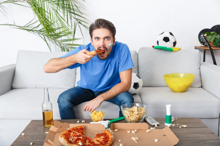 Young man sport fan watching match in a blue t-shirt eating pizza
