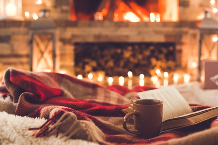 One cup and a book near the fireplace winter concept Foto de archivo
